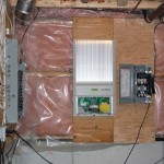 The solar inverter (center) and disconnect switch (right) mounted in the basement next to the electrical panel.